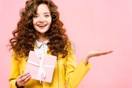 Photo pour Belle coquine tenant un cadeau et présentant quelque chose, isolée sur rose - image libre de droit
