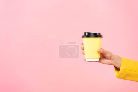 Photo pour Vue en coupe d'une femme tenant une tasse de café jaune jetable, isolée en rose - image libre de droit
