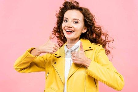 Photo pour Fillette à la mode vêtue d'une veste de cuir jaune avec les pouces relevés, isolée en rose - image libre de droit