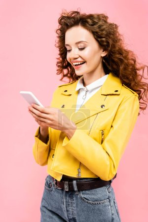 happy curly girl using smartphone, isolated on pink