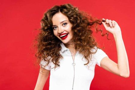 Photo pour Attractive happy curly fille isolée sur rouge - image libre de droit