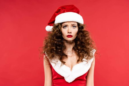 Photo pour Upset curly girl posing in santa costume, isolated on red - image libre de droit