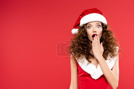 Photo for Happy surprised girl gesturing in santa costume, isolated on red - Royalty Free Image