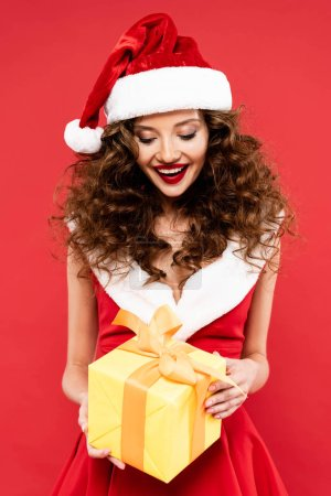 Photo for Cheerful attractive girl in santa costume holding christmas gift, isolated on red - Royalty Free Image