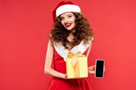 Photo for Attractive smiling girl in santa costume holding christmas gift and smartphone with blank screen, isolated on red - Royalty Free Image