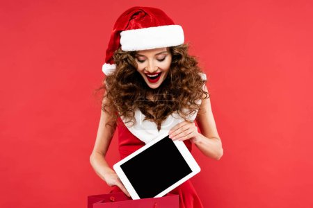 Photo for Cheerful girl in santa costume holding shopping bag with digital tablet, isolated on red - Royalty Free Image