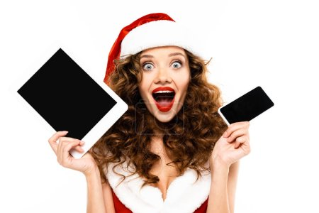 Photo for Excited curly woman in santa costume holding digital devices with blank screens, isolated on white - Royalty Free Image