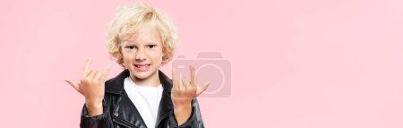 Photo pour Plan panoramique d'un enfant souriant montrant un panneau de roche isolé sur rose - image libre de droit