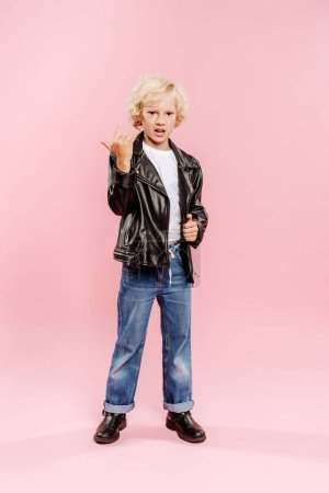 Photo pour Kid in leather jacket showing rock sign on pink background - image libre de droit