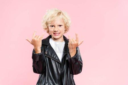 Photo pour Enfant souriant en veste en cuir montrant signe de roche isolé sur rose - image libre de droit