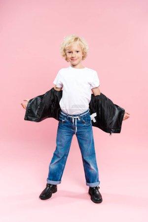 Photo pour Enfant souriant en veste en cuir regardant la caméra sur fond rose - image libre de droit