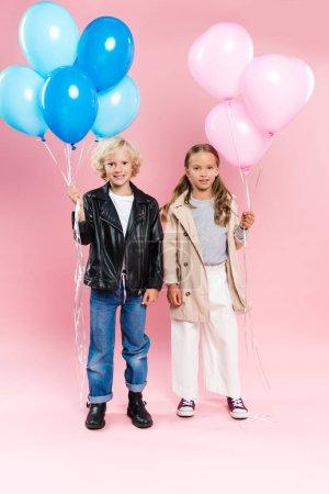 Foto de Niños sonrientes y lindos que tienen globos sobre fondo rosado. - Imagen libre de derechos