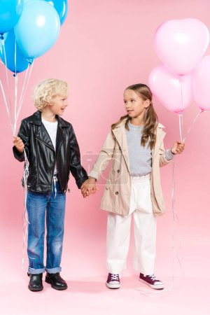 Foto de Smiling kids holding balloons and holding hands on pink background - Imagen libre de derechos
