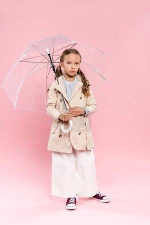 Photo pour Enfant en tenue d'automne tenant parapluie sur fond rose - image libre de droit