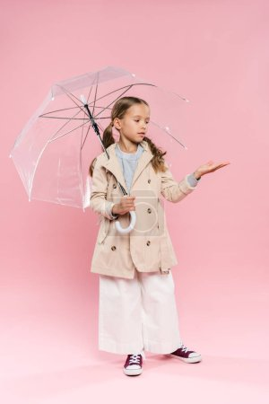 Photo for Kid in autumn outfit with outstretched hand holding umbrella on pink background - Royalty Free Image
