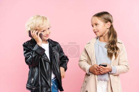 Photo pour Enfants souriants et mignons tenant et parlant sur smartphone sur fond rose - image libre de droit