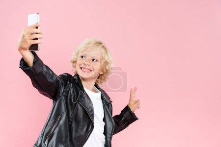 Photo pour Smiling kid taking selfie and showing peace sign isolated on pink - image libre de droit
