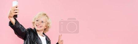 Photo pour Plan panoramique d'un enfant souriant prenant un selfie et montrant un signe de paix isolé sur rose - image libre de droit