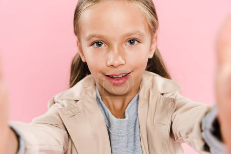 Photo pour Foyer sélectif de sourire enfant regardant la caméra isolée sur rose - image libre de droit