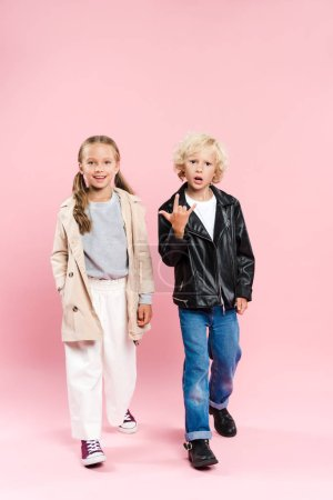 Photo pour Kids smiling and showing rock sign on pink background - image libre de droit