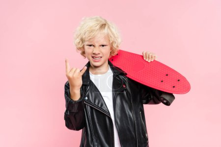 Photo pour Cute kid showing rock sign and holding penny board isolated on pink - image libre de droit