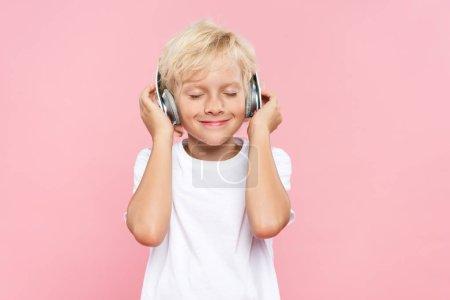 Photo pour Enfant souriant avec écouteurs écoutant de la musique isolée sur rose - image libre de droit