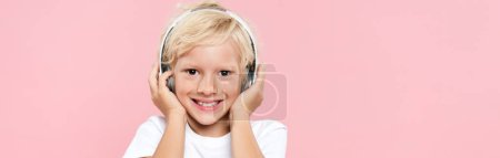Photo pour Panoramic shot of smiling kid with headphones listening music isolated on pink - image libre de droit