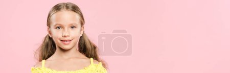 Photo pour Plan panoramique d'un enfant souriant regardant une caméra isolée sur rose - image libre de droit