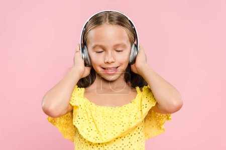 Photo for Smiling kid with headphones listening music isolated on pink - Royalty Free Image
