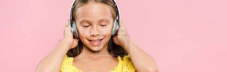 Photo pour Plan panoramique d'un enfant souriant avec écouteurs écoutant de la musique isolée sur rose - image libre de droit