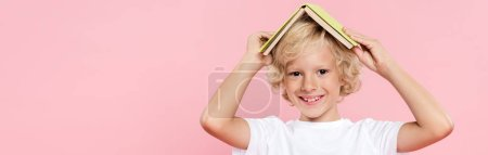 Photo for Panoramic shot of smiling kid holding book isolated on pink - Royalty Free Image