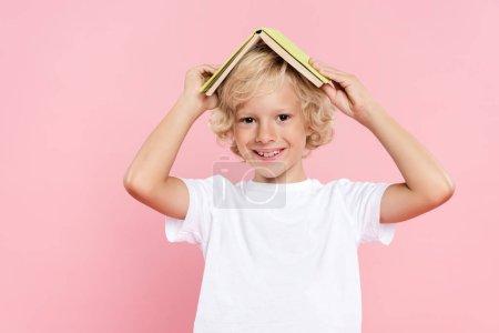 Photo pour Enfant souriant tenant livre et regardant la caméra isolée sur rose - image libre de droit