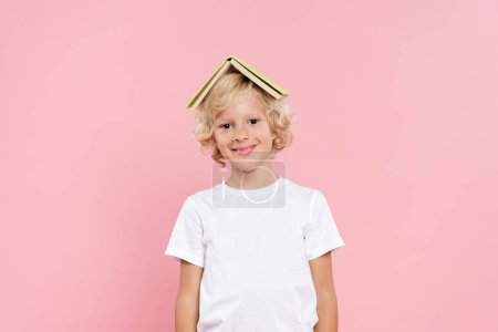Photo for Smiling kid with book on head isolated on pink - Royalty Free Image