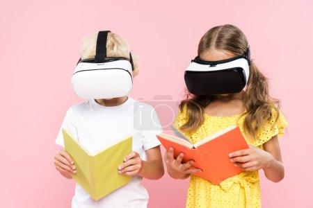 Photo pour Enfants avec casque de réalité virtuelle livre de lecture isolé sur rose - image libre de droit