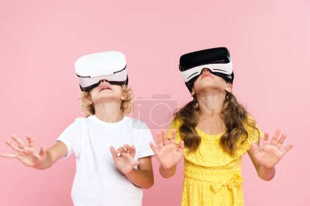 Photo pour Kids with virtual reality headset and outstretched hands looking up on pink background - image libre de droit