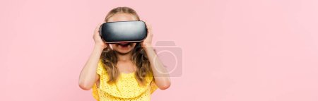 panoramic shot of smiling kid with virtual reality headset isolated on pink