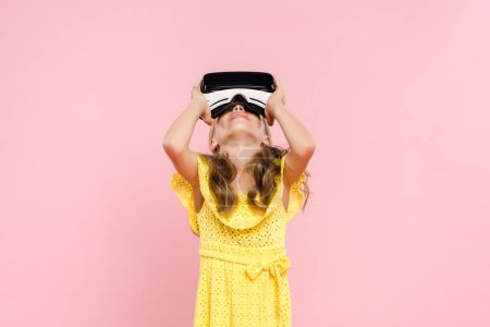 kid with virtual reality headset looking up isolated on pink