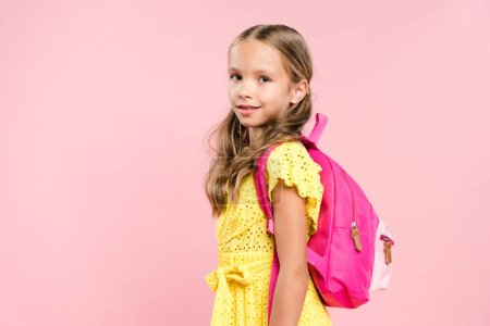 smiling schoolgirl with backpack looking at camera isolated on pink