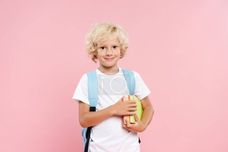 Photo pour Écolier souriant avec sac à dos tenant des livres isolés sur rose - image libre de droit