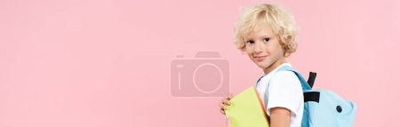 panoramic shot of smiling schoolboy with backpack holding book isolated on pink