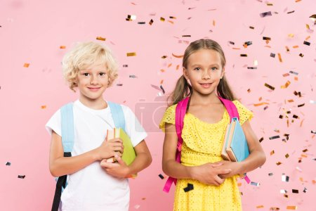 Photo for Smiling schoolchildren with backpacks holding books near falling confetti - Royalty Free Image