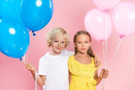 Foto de Niños sonrientes y lindos abrazando y sosteniendo globos sobre fondo rosado. - Imagen libre de derechos