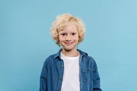 Photo pour Souriant et mignon enfant regardant caméra isolée sur bleu - image libre de droit