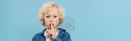 Photo pour Panoramic shot of cute kid showing secret gesture and looking at camera isolated on blue - image libre de droit