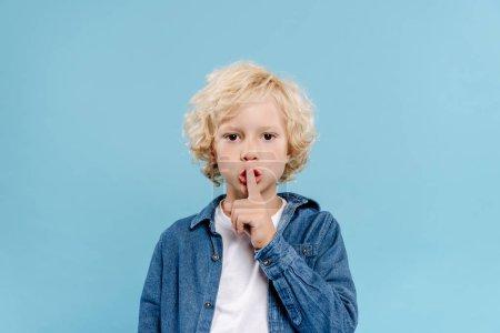 Photo pour Mignon enfant montrant geste secret et regardant caméra isolé sur bleu - image libre de droit