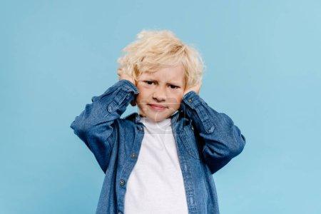 Photo pour Irrité et mignon enfant touchant les oreilles et regardant la caméra isolé en bleu - image libre de droit