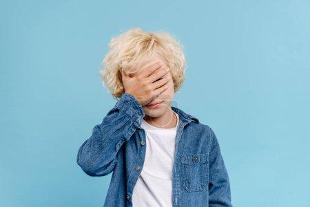 Photo pour Fatigué et mignon enfant obscurcissant visage isolé sur bleu - image libre de droit