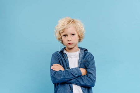 sad and cute kid with crossed arms looking at camera isolated on blue