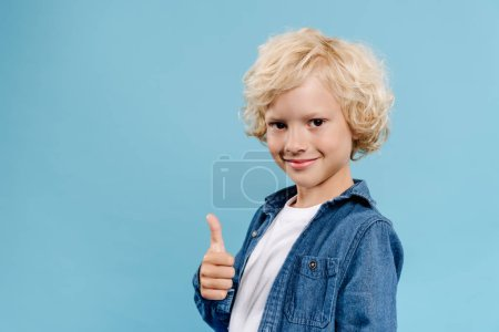 smiling and cute kid looking at camera and showing like isolated on blue