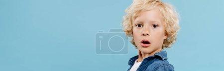 Photo pour Plan panoramique d'enfant choqué et mignon regardant la caméra isolée sur bleu - image libre de droit
